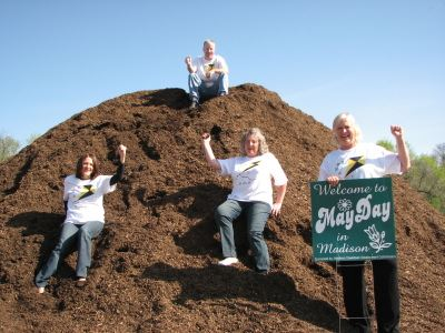 4 adults holding May Day poster on mound of mulch