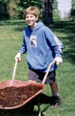 Boy pushing wheelbarrow full of mulch