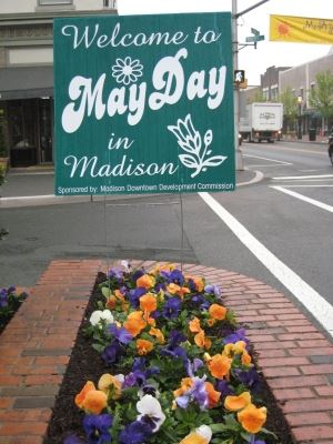 May Day welcome sign in front of flowers